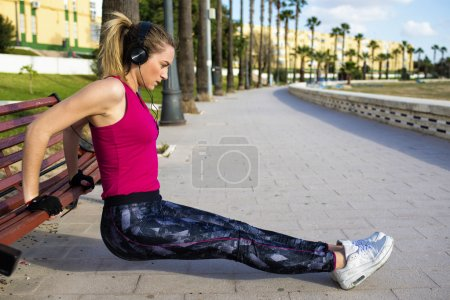 Photo for Young blonde woman stretching on a park bench while listening to music - Royalty Free Image
