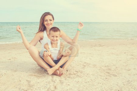 Happy family. Young happy beautiful  mother and her son doing yoga on coast of sea on beach.