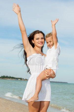 Photo pour Famille heureuse. Jeune heureuse belle mère et sa fille s'amuser sur la plage. Les émotions humaines positives, les sentiments, les émotions. - image libre de droit