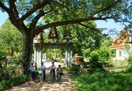 Group Asian kids, riding bike, Khmer village gate