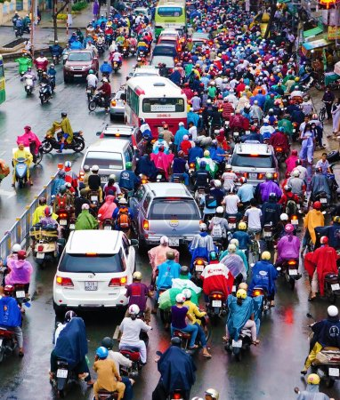 Photo for HO CHI MINH CITY, VIET NAM- OCT6: Impression, colorful scene of Asia city in rush hour after rain evening, crowd of Vietnamese people wear raincoat, on motorbike, crowded on street, Vietnam, Oct6,2014 - Royalty Free Image