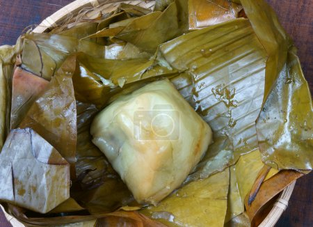 Photo for Vietnamese food, name Banh Gio: pyramid shaped rice dough dumpling filled with pork, shallot, and wood ear mushroom wrapped in banana leaf, is delicious street food, diet food make from rice flour - Royalty Free Image