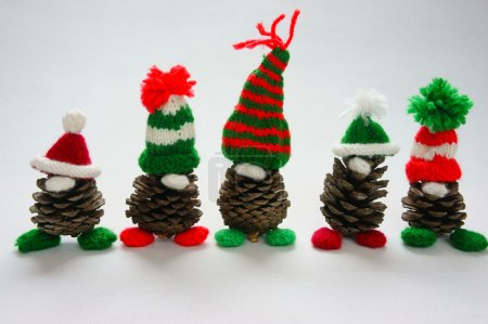 Photo for Christmas pine gnome on white background, Xmas pinecone wear Xmas hat for decoration on winter holiday, with red, green yarn, homemade product by knitted hat, food, nose make amazing and pretty gift - Royalty Free Image