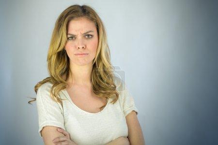Photo pour Attrayant femme en colère avec les bras croisés sur fond plat tourné en studio avec un éclairage dramatique - image libre de droit