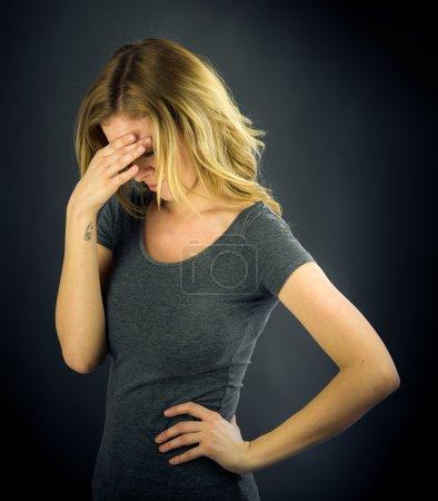 Photo pour Belle femme honteuse cachant visage dans la main sur fond plat tourné en studio avec un éclairage dramatique - image libre de droit