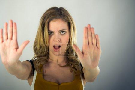 Photo pour Belle femme gestuelle stop signe avec les mains sur fond plat tourné en studio avec des lumières douces - image libre de droit