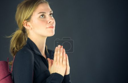 Photo for Attractive woman praying and wishing on plain background shot in studio with soft lights - Royalty Free Image