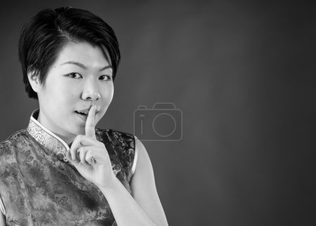 Woman asking for silence with finger on lips