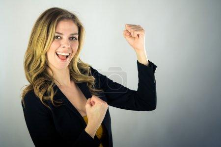 Photo pour Belle femme célébrant avec les poings vers le haut sur fond plat tourné en studio avec des lumières douces - image libre de droit