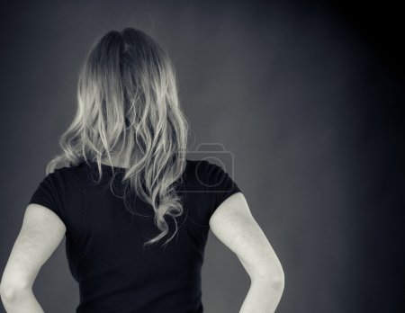 Photo for Rear view of attractive woman with hands on hips  on plain background shot in studio with soft lights. Photo made in black and white colors - Royalty Free Image