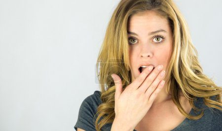 Shocked woman covering her mouth by hand