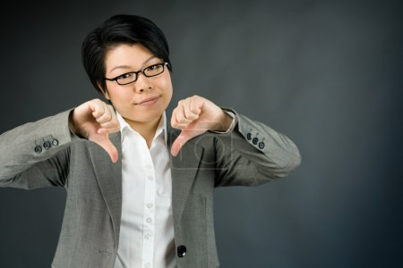 Woman gesturing thumbs down sign