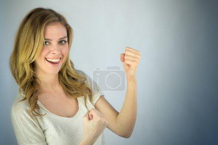 Photo pour Belle femme célébrant le succès avec les poings vers le haut sur fond plat tourné en studio avec un éclairage dramatique - image libre de droit