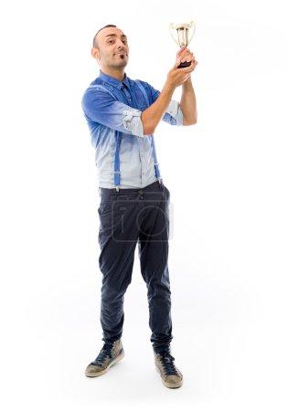 Photo pour Modèle tenant un trophée et célébrant le succès en studio isolé sur fond blanc uni - image libre de droit