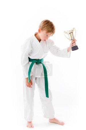 Photo pour Garçon tenant un trophée en studio isolé sur fond blanc uni - image libre de droit