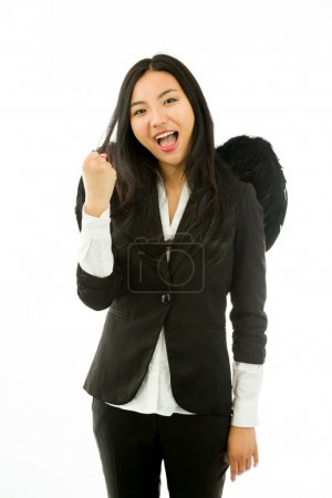 Excited Asian young businesswoman dressed up as a black angel celebrating success with fist up isolated on  white background