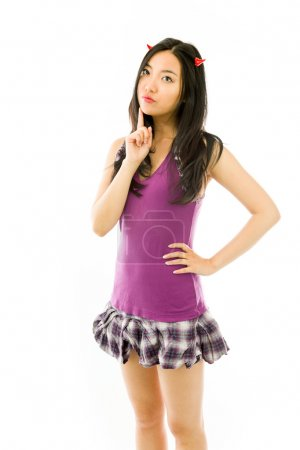 Asian young woman dressed up as a devil  and standing with hand on hip isolated on white background