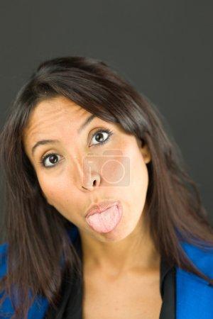 Portrait d'une jeune femme d'affaires qui sort sa langue