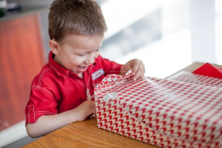 Excited little boy opening his birthday gift
