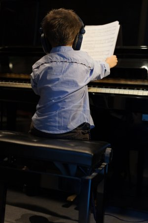 Rear view of a little boy learning piano