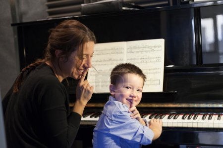 Boy putting index finger on lips with his piano instructor and smiling