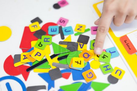 Close up of a persons hand showing multi-coloured alphabet puzzle pieces