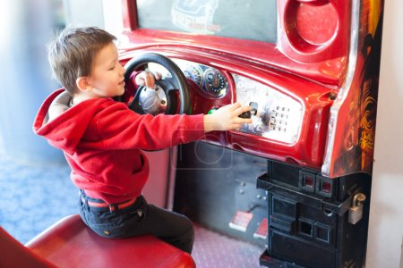 Side view of a little boy playing driving game at video game arcade