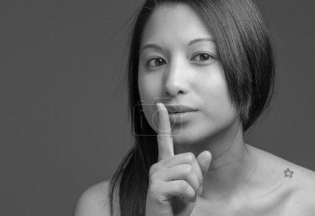 Photo pour Modèle avec un doigt sur les lèvres isolé sur fond uni en studio - image libre de droit