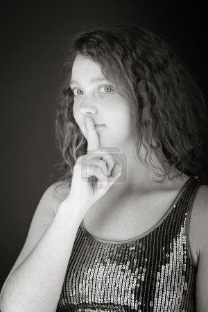 Modell mit Finger auf den Lippen