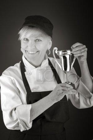 Photo pour Modèle tenant un trophée en studio isolé sur fond gris uni - image libre de droit