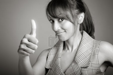 Businesswoman making thumb up sign