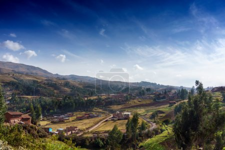 Village on hill against cloudy sky