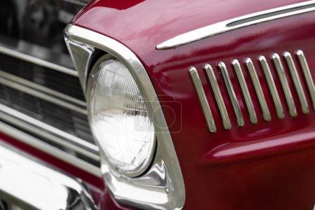 Right headlight of a shiny vintage car