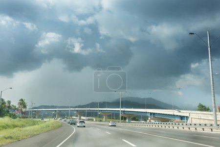Traffic on road against cloudy sky