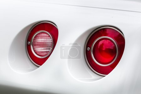 Red tail lights of a white vintage car