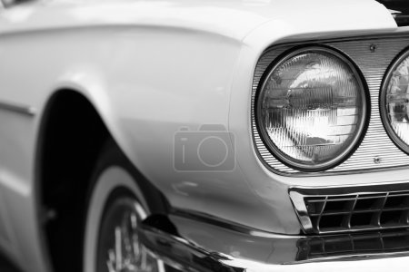 Left headlights of a white vintage car
