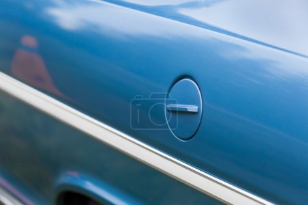Petrol tank of a blue shiny vintage car