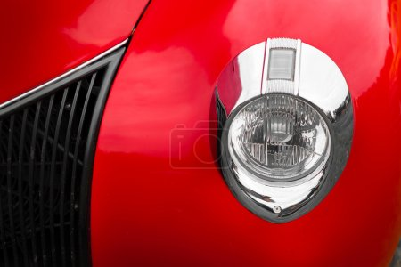Right headlight of a red vintage car