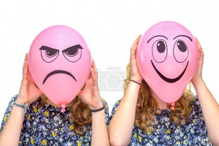 Photo for Two girls holding pink balloons with facial expressions of frustrated and smiling face isolated on white background - Royalty Free Image