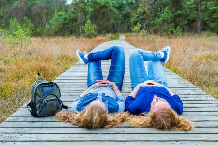 Two girls lying on their backs on path in nature