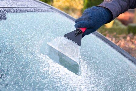 Photo pour Main portant un gant qui gratte la glace de la fenêtre de la voiture avec du givre en hiver - image libre de droit