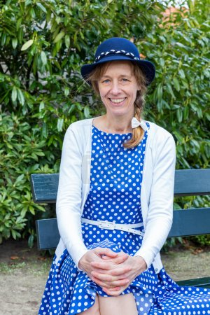 Dutch woman in old-fashioned clothes sitting on bench in park
