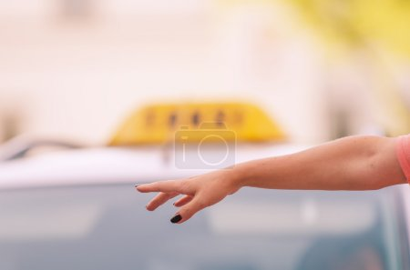 Woman raising her arm to call a taxi...