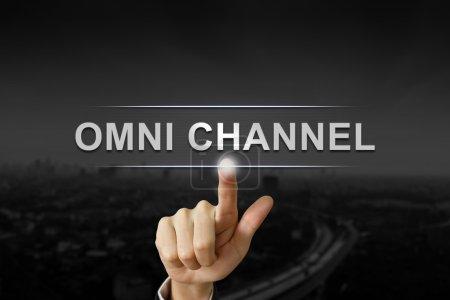 Photo pour Main d'affaires en cliquant sur le bouton omni canal sur fond noir flou - image libre de droit