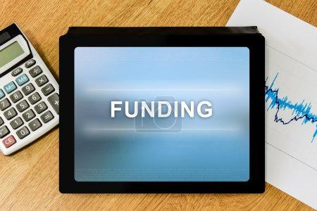 Photo pour Mot de financement sur tablette numérique avec calculatrice et graphique financier - image libre de droit