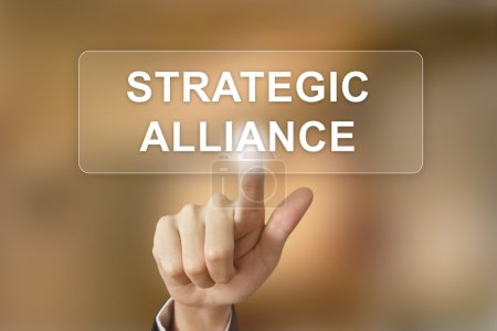 Business hand clicking strategic alliance button on blurred back