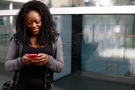 Photo for Young African woman sending an sms on her mobile smiling as she types in the text with her thumbs on the touch screen in front of an urban building - Royalty Free Image