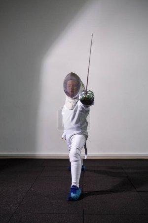 Photo pour Une fille en costume d'escrime avec une épée à la main. Jeune modèle féminin pratiquant et exerçant. Sport, mode de vie sain. - image libre de droit