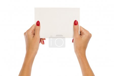 Photo for Close up of two woman's hands with red nails holding blank white paper sheet. Studio shot isolated on white. - Royalty Free Image