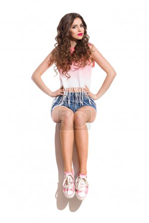 Photo for Young woman in pink sneakers, pink top and jeans shorts sitting on the top of white banner with hands on hip. Full length studio shot isolated on white. - Royalty Free Image